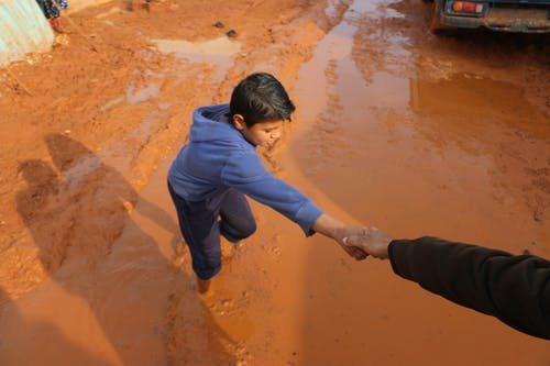 High angle of crop person holding hands with ethnic boy stuck in dirty puddle in poor village