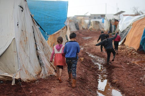 Children walking on dirty street with tents