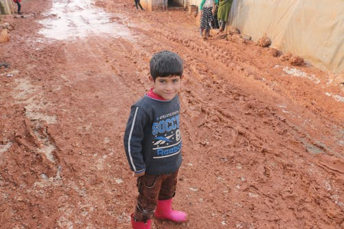 From above of glad ethnic kid inc casual wear standing on dirty path near tents in poor district of refugee camp