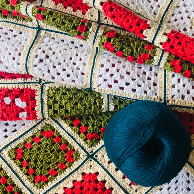 Blue Yarn on White Red and Green Textile