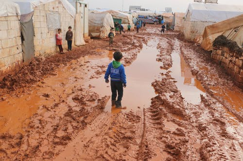 Group of children standing on dirty wet ground with puddles between old tents in refugee camp with in poor settlement