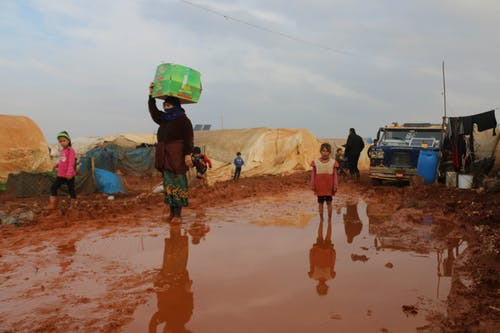 Ethnic children and adults refugees walking on dirty ground