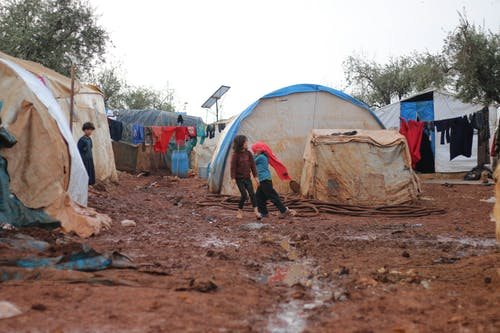 Carefree children playing on dirty wet ground near worn out tents in poor district with trash and hanging colorful clothes