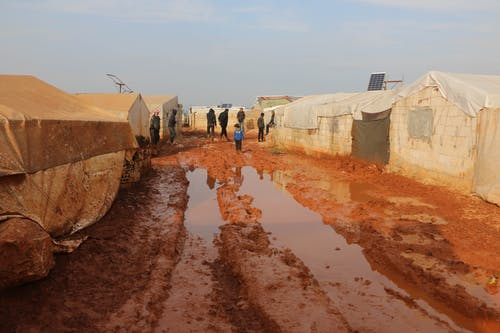 Group of distant adults and kids strolling on wet dirty ground with puddles near worn out tents in poor area