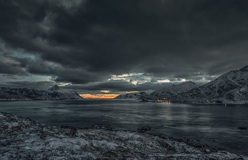 Body of Water Near Mountain Under Gray Clouds during Sunset