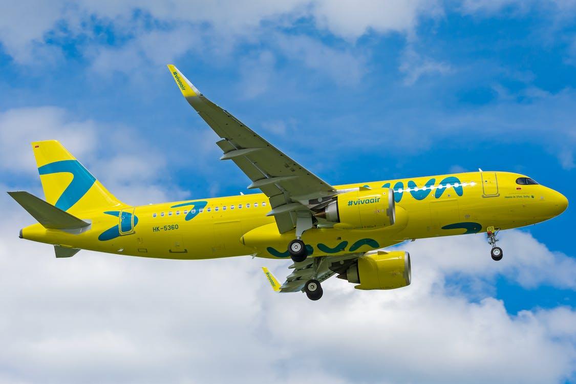 Blue and White Passenger Plane Flying Under Blue Sky - Air travel