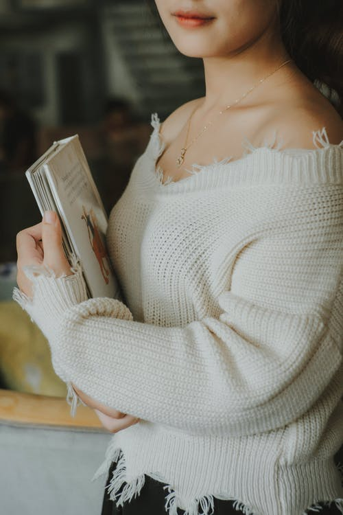 Woman in White Knit Sweater Holding Book