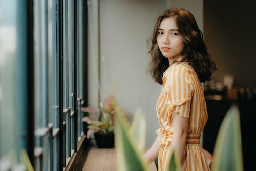 Charming Asian female standing near window