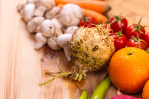 Close-Up Shot of Fresh Vegetables and Fruits on a Wooden Table