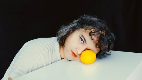 Girl in White and Gray Striped Long Sleeve Shirt Holding Orange Fruit