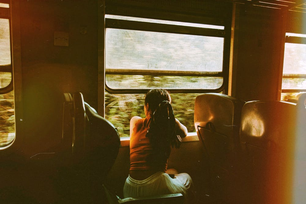 Woman riding train and looking out window.   Photo: Pexels