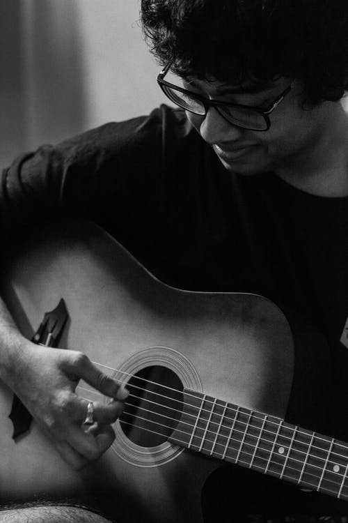 Grayscale Photo of a Man Playing Acoustic Guitar