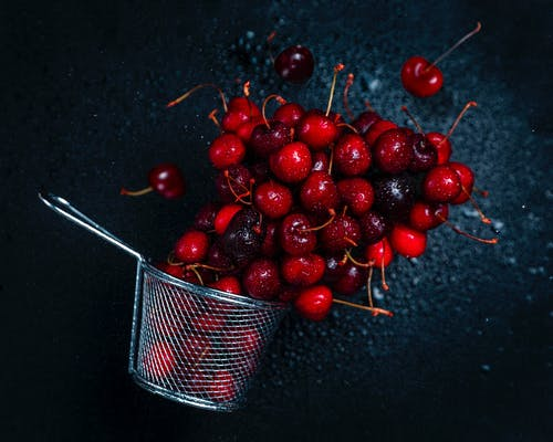 Top view composition of delicious sweet cherries and strainer scattered on dark background in studio