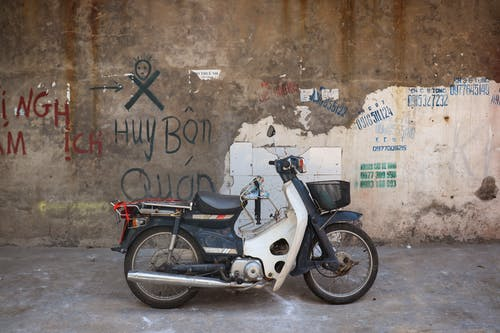 White and Black Motorcycle Parked Beside Wall