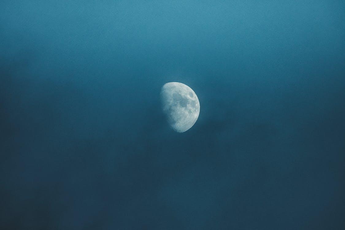 Waxing white moon with gray spots illuminating on foggy sky at bright night