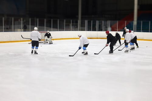 People Playing Hockey on Ice Rink