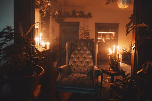 Room interior with armchair between glowing candles