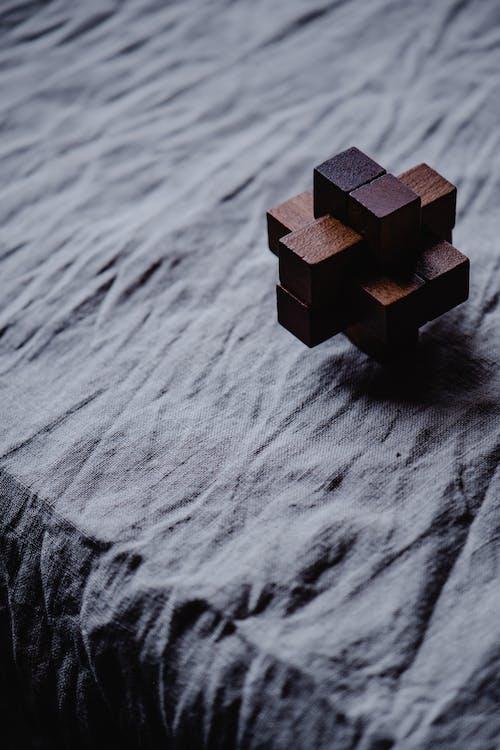 Cubo Di Legno Marrone Su Tessuto Grigio
