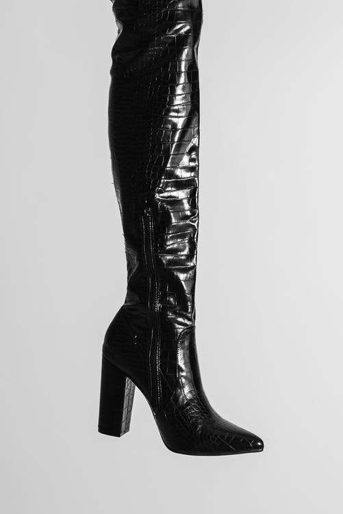 Crop unrecognizable stylish female leg in black leather boot on high heels in light studio