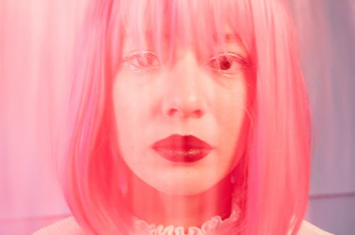 Crop unemotional woman with pink hair in studio