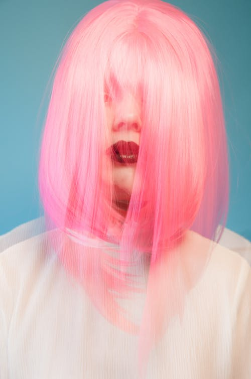 Double exposure unemotional female with bright makeup covering face with pink hair standing against blue background in studio