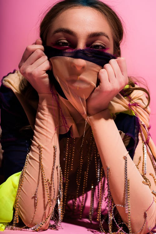 Crop woman in creative fashionable clothes covering face with cloth