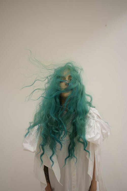 Unemotional fit female wearing white loose dress standing with eyes closed and flying long green hair against white wall in studio