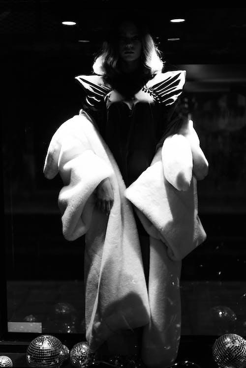 Confident woman in fur standing in dark studio