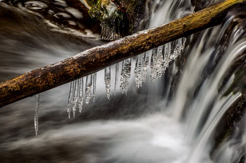 Wet stick with icicles before huge waterfall