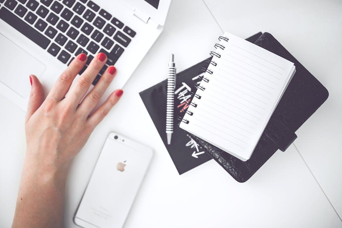 Laptop putih, tangan wanita, catatan, pena, telepon, meja