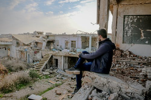 Unrecognizable man sitting on damaged ruins of building