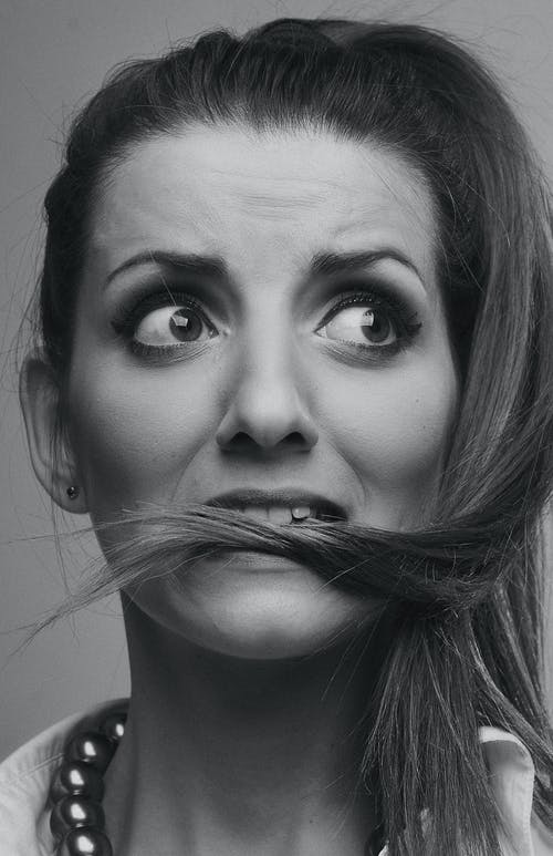 Grayscale Photo of Woman Biting Her Hair