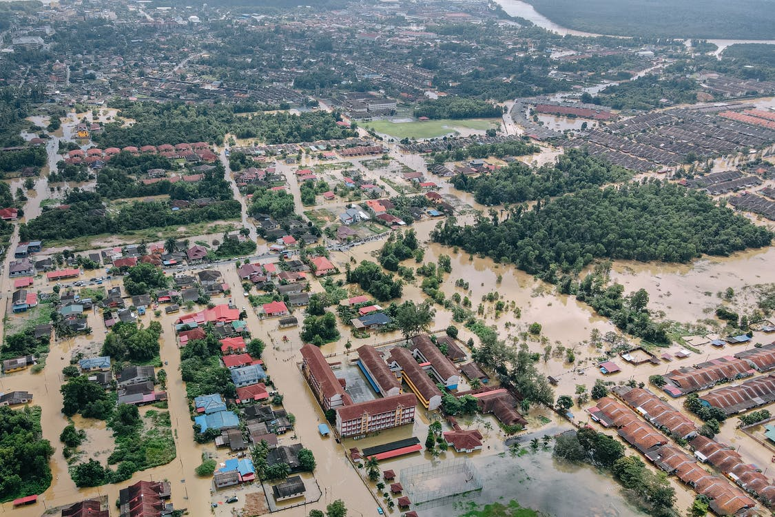 Aerial view of flooded small town with many residential houses and lush green trees