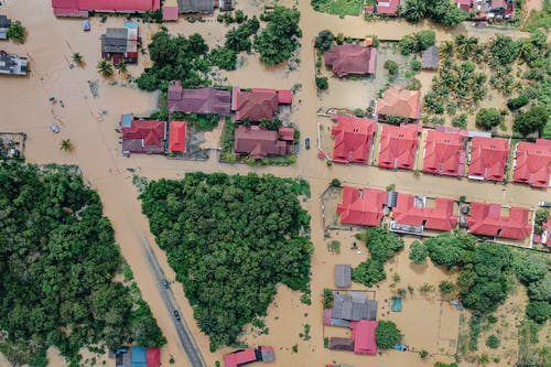 Overhead view of colorful roofs of residential buildings and lush green trees in flooded small village