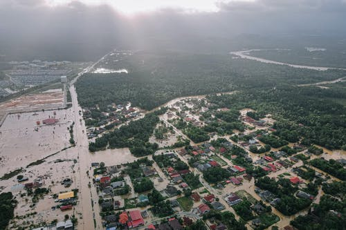 Aerial view of many residential houses and lush green trees in flooded small city
