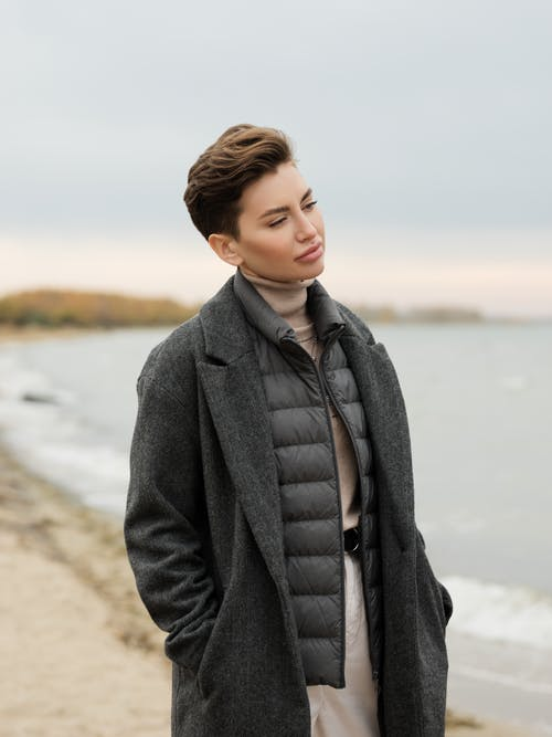 Woman in Black Coat Standing on Brown Sand
