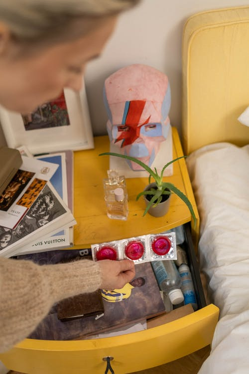 A Person Discovering Three Pink Condoms from a Bedside Table