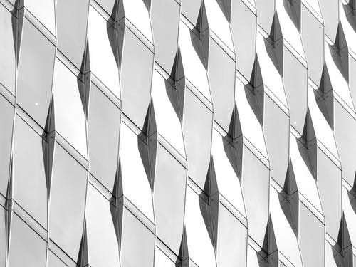 From below black and white of modern skyscraper facade with glass uneven windows in city street in daytime