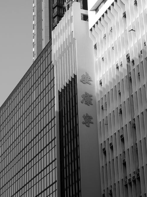 From below black and white of contemporary multistory building exterior with hieroglyphs on wall in daylight in city street under bright sky