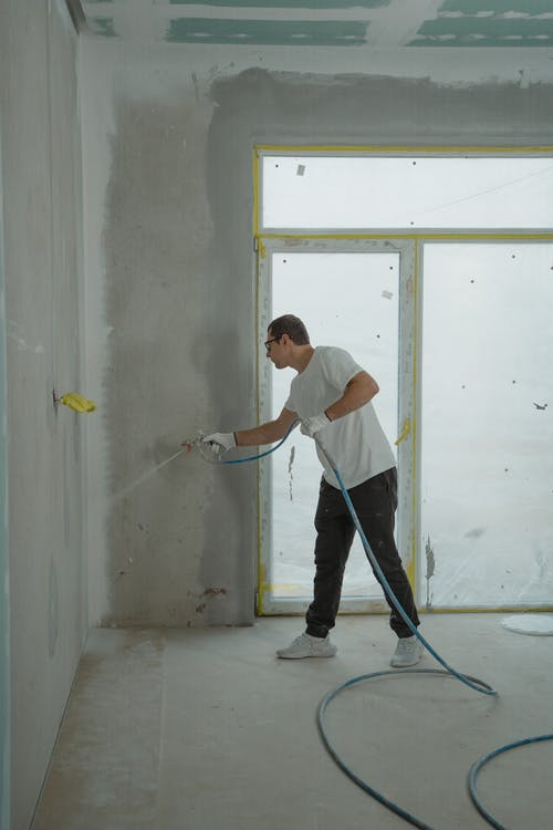 Man in White Dress Shirt and Black Pants Holding a Spray Hose