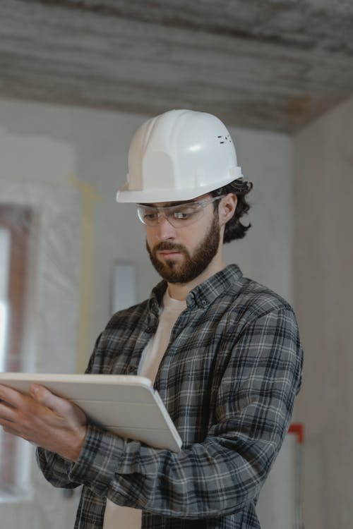 Man in Blue and White Plaid Button Up Shirt Wearing White Hard Hat