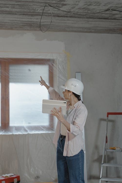Woman Pointing to the Window while Holding the Ipad