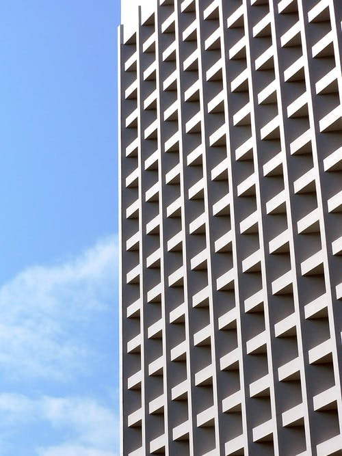 Facade of modern tall building under blue sky