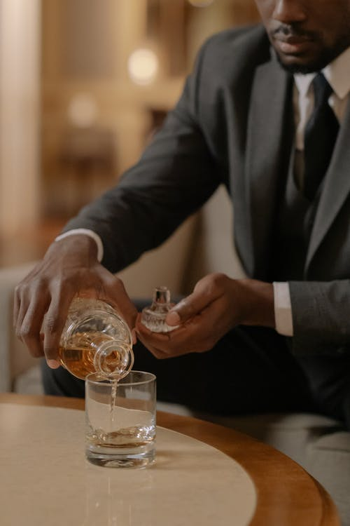 Man in Black Suit Holding Clear Drinking Glass