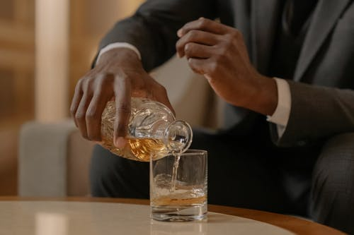 Man in Black Suit Jacket Holding Clear Drinking Glass