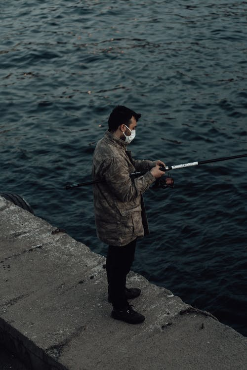 Side view full body of anonymous man in outerwear and mask standing on stone border near rippling ocean while fishing with rod in daytime