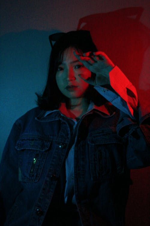 Young ethnic female covering face from neon light