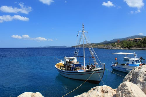 White and Blue Boat on Sea Under Blue Sky