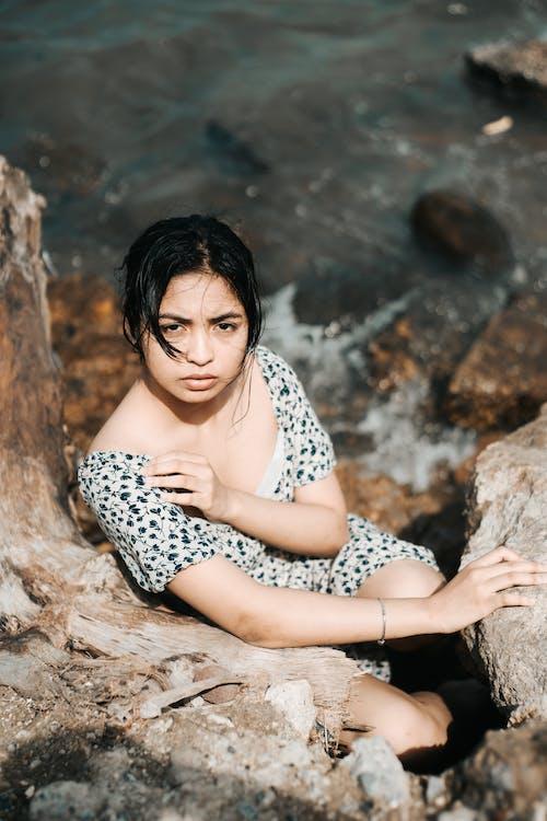Female traveler between rocks on sea shore