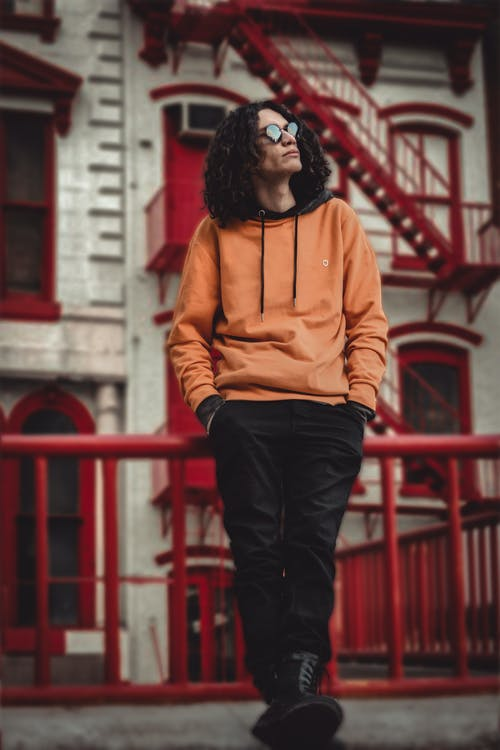 Man Leaning on Red Railings